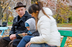 Family outing to the park. Family outing park with elderly grandfather , his daughter and grandson sitting park bench warmly dressed against the autumn chill stock photo