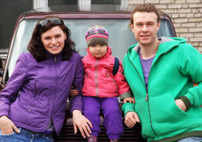 Family in outwear leaning on car Stock Photos