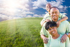 Family Over Clouds, Sky and Grass Field. Happy African American Family Over Clouds, Sky and Arched Horizon of Grass Field Stock Photos