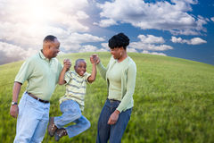Family Over Clouds, Sky and Grass Field. Happy African American Family Playing Over Clouds, Sky and Arched Horizon of Grass Field Stock Photography