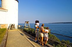 Family overlooking ocean. A view of a family on vacation, sightseeing at the Bass Harbor Lighthouse, Maine, stopping to take in the scenery along the beautiful Royalty Free Stock Photography