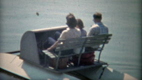 1968: Family packed into a paddleboat on a pond. WASHINGTON DC. Original vintage 8mm film home movie professionally cleaned and captured in 4k (3840x2160 UHD) stock video