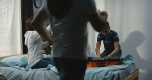 Family packing in bedroom. Medium long shot of family packing in bedroom stock video footage