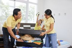 Family packing suitcase stock image