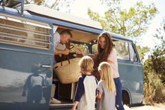 Family packing up their camper van for a road trip vacation stock photos