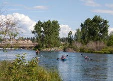 Family Paddle Boarding And Canoeing In River. A family stand up paddle boarding and canoeing enjoying a nice day in the Deschutes River royalty free stock images