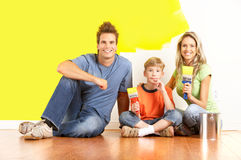 Family painting. Smiling young family painting interior wall of home Royalty Free Stock Images