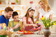 Family painting colorful eggs and preparing for Easter Royalty Free Stock Photos