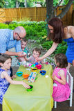 Family Painting and Dyeing Easter Eggs Together. A family picture of children painting and decorating eggs.  A mother and father help their children together at Royalty Free Stock Image