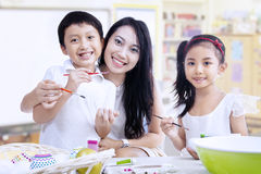 Family painting eggs in class. Mother and children are painting in a classroom Royalty Free Stock Image