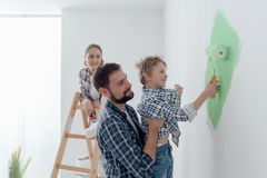 Family painting a room together. Happy young family renovating their home, the father is holding his son and he is helping him to paint a wall with a paint Stock Photos