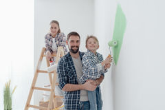 Family painting a room together. Happy young family renovating their home, the father is holding his son and he is helping him to paint a wall with a paint Stock Image