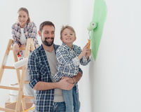 Family painting a room together. Happy young family renovating their home, the father is holding his son and he is helping him to paint a wall with a paint Royalty Free Stock Image