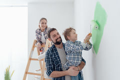 Family painting a room together. Happy young family renovating their home, the father is holding his son and he is helping him to paint a wall with a paint royalty free stock photos