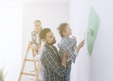Family painting a room together. Happy young family renovating their home, the father is holding his son and he is helping him to paint a wall with a paint Stock Images
