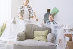 Family painting their home. Happy young family renovating their home, they are covering the furnishings with a protective plastic sheet and painting the walls stock photo
