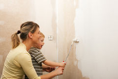 Family painting wall of new home Royalty Free Stock Image