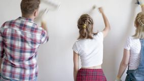 Family painting wall in room. Father, mother and daughter painting wall in apartment room. Beautiful young family doing repairs in new flat. Parents and teen stock video footage