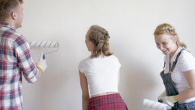 Family painting wall in room stock video footage
