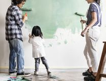 Family painting wall together with brush stock images