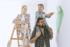 Family painting walls together. Happy family renovating their new home, the father is piggybacking his son and helping him painting with a roller, the mother is stock images