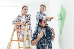 Family painting walls together. Happy family renovating their new home, the father is piggybacking his son and helping him painting with a roller, the mother is Royalty Free Stock Photos