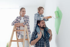 Family painting walls together. Happy family renovating their new home, the father is piggybacking his son and helping him painting with a roller, the mother is stock image