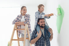 Family painting walls together. Happy family renovating their new home, the father is piggybacking his son and helping him painting with a roller, the mother is Royalty Free Stock Images