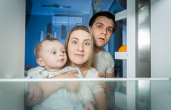 Family in pajamas looking inside the refrigerator for something. Portrait of family in pajamas looking inside the refrigerator for something to eat Royalty Free Stock Photography