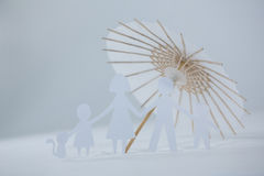 Family paper cut-out figures with cocktail umbrella. On white background Royalty Free Stock Photos