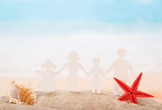 Family of paper, seashell and star in sand against sea. Royalty Free Stock Images