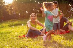 Family, parenthood, adoption and people concept – Happy family. Family, parenthood, adoption and people concept - Happy family with little children blow stock photo