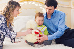 Family, parenthood and children concept - Close-up of happy mother, father and son playing together with teddy bear on Stock Photos
