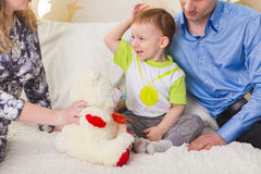 Family, parenthood and children concept - Close-up of happy mother, father and son playing together with teddy bear on Royalty Free Stock Photography