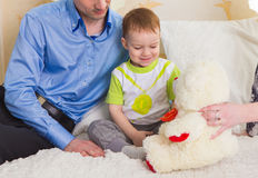 Family, parenthood and children concept - Close-up of happy mother, father and son playing together with teddy bear on Royalty Free Stock Image