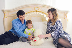 Family, parenthood and children concept - Happy mother, father and son playing together with teddy bear on bed in Stock Photography