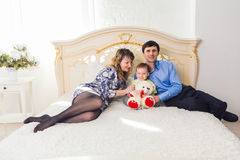 Family, parenthood and children concept - Happy mother, father and son playing together with teddy bear on bed in Stock Photo