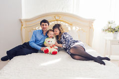 Family, parenthood and children concept - Happy mother, father and son playing together with teddy bear on bed in stock photos
