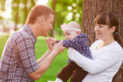 Family parenthood concept - happy mother father and little girl playing in summer park Royalty Free Stock Photos