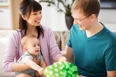 Mother with baby giving birthday present to father. Family, parenthood and fathers day concept - happy mother with baby boy giving birthday present to father at royalty free stock images