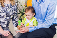Family, parenthood, happy birthday and holiday concept - close-up happy mother and father and child with cake. Family, parenthood, happy birthday and holiday royalty free stock image