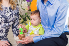 Family, parenthood, happy birthday and holiday concept - close-up happy mother and father and child with cake. Family, parenthood, happy birthday and holiday royalty free stock images