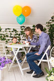 Family, parenthood, happy birthday and holiday concept - happy parents and child at a table drinking tea and eating cake.  royalty free stock photography