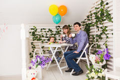 Family, parenthood, happy birthday and holiday concept - happy parents and child at a table drinking tea and eating cake.  royalty free stock image
