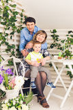 Family, parenthood, happy birthday and holiday concept - portrait of happy parents and child at a table drinking tea and. Family, parenthood, happy birthday and royalty free stock photo