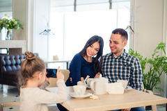 Family, parenthood, technology people concept - close up of happy mother, father and little girl having dinner, kid stock photography