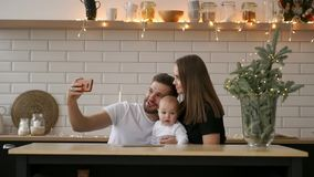 Family, parenthood, technology and people concept - happy mother, father and little boy having dinner and taking selfie. Family, parenthood, technology and stock footage