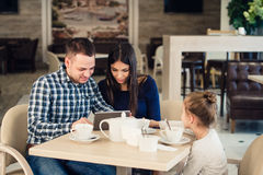 Family, parenthood, technology people concept - happy mother, father and little girl with tablet pc computer having royalty free stock photos