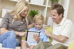 Family Parents & Boy Son Using Tablet Computer. A young family of men and women parents and one boy child, using a tablet computer at home on a sofa royalty free stock photos