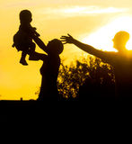 Family parents and child silhouette by sunset Royalty Free Stock Photo